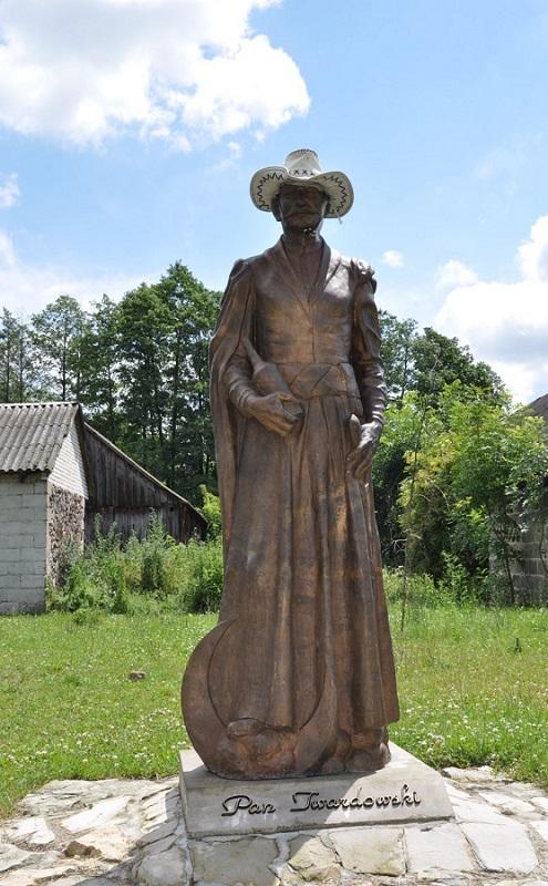 Stojaca postać człowieka z wykonana z brazu - Pan Twardowski. Ma na głowie biały kapelusz.