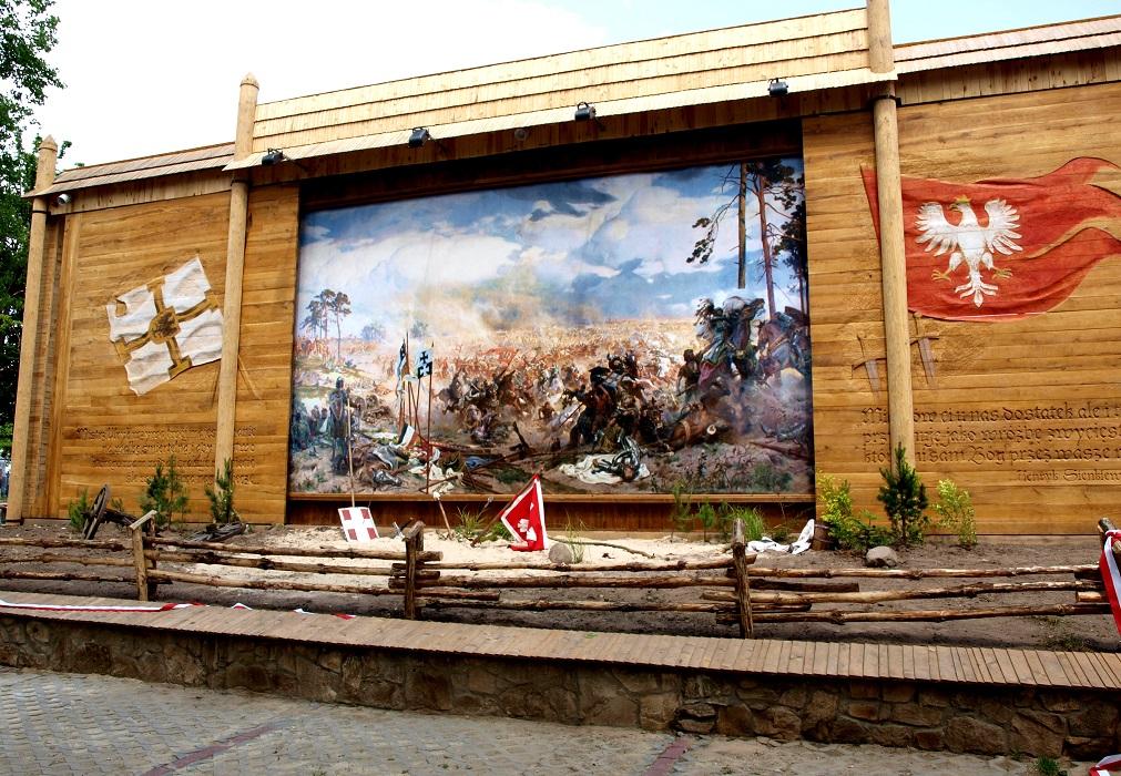 Obraz przedstawiajacy bitwe wojsk pod Grunwaldem. osadonyy w specjalnej teatralnej konstrukcji z drewna. Po lewo i prawo prztwierdzone dwie flagi.