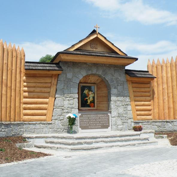 Kaplica z białych kamieni. Przykryta drewnianym dachem. Z boku drewniana obudowa. W środku obraz.